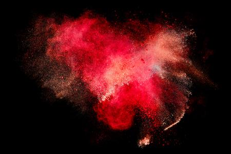 Colorful esplosione di particelle di polvere simile a sangue o un effetto pirotecnico sul nero. Abstract background. Primo piano di una esplosione di colore isolati su nero Archivio Fotografico