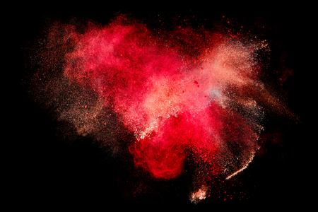 Colorful dust particle explosion resembling blood or a pyrotechnic effect over black. Abstract background. Closeup of a color explosion isolated on black Stockfoto