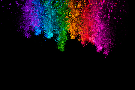 Falling colored powder. Rainbow of purple, blue, green, yellow, red and pink dust over black background with copy space for text