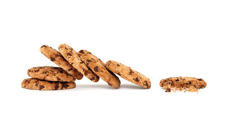 deliciously: Side view on collapsed stack of six yummy chocolate chip cookies next to a partially eaten one with crumbs, isolated on white background with copy space Stock Photo