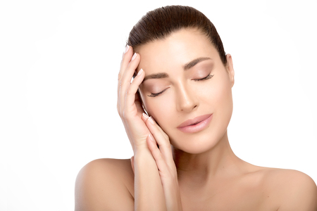 Skincare and spa concept. Gorgeous natural young woman with a smooth unblemished complexion and bare shoulders with hands raised gracefully to her cheek posing with her eyes closed in a head and shoulders beauty portrait isolated on white.
