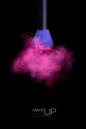 black makeup: Makeup concept with a single blue makeup brush shaking or applying pink powder. Colorful dust explosion. Isolated on black background with copy space and sample text
