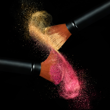 Makeup concept. Stop action view of two makeup brushes applying matching red and gold powder over black background