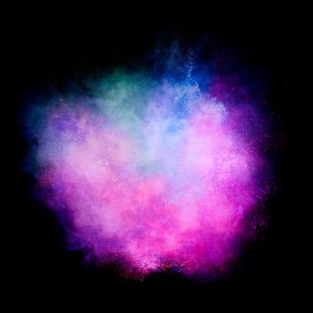 polvo: explosión de partículas de polvo colorido se asemeja a un efecto pirotécnico sobre fondo negro. Primer plano de una explosión de color aislado en negro