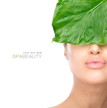 スパとビューティーのコンセプトで目と鼻をカバーする新鮮な葉を半分の顔の女性。美しさの肖像画のコピーのテキストのための領域を白で隔離 写真素材