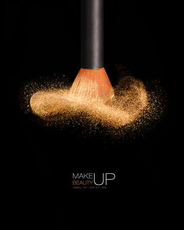 Makeup concept with a single professional makeup brush with glowing face powder isolated on black background with copy space and sample text