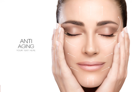 arrugas: el tratamiento contra el envejecimiento y el concepto de la cirugía plástica. Joven y bella mujer con las manos en las mejillas y los ojos cerrados con una expresión serena y flechas blancas sobre el rostro. Foto de archivo