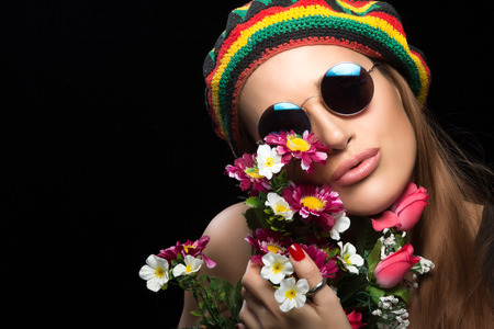 rasta hat: Close-up of beautiful young woman wearing rasta hat and sunglasses while holding colorful flowers. Close-up portrait isolated on black background with copy space