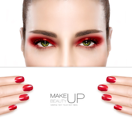 Beauty Makeup and Nai Art Concept. Beautiful fashion model woman with red smoky eye makeup to match her manicured nails, foundation on a unblemished skin, half face with a white card template. High fashion portrait isolated on white
