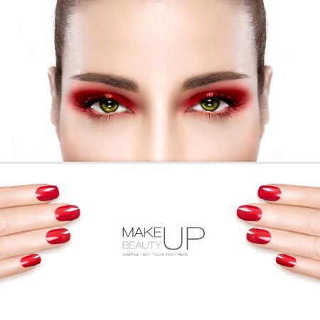 Schönheit Make-up und Nai Art Concept. Schöne Mode Modell Frau mit roten rauchigen Augen Make-up ihr gepflegte Nägel, Fundament, auf eine makellose Haut, halbe Gesicht mit einer weißen Karte Vorlage übereinstimmen. Hohe Art und Weise Porträt isoliert auf weiß