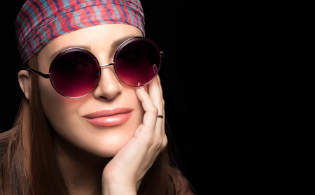 head scarf: Gorgeous young woman in a head scarf and trendy round sunglasses resting her chin on her hand smiling at the camera over a dark background with copy space Stock Photo