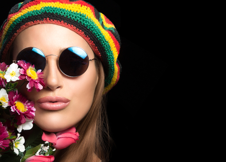 rasta hat: Close up on face of beautiful young woman in hippie style with round sunglasses rasta hat and flowers near lips over black background with copy space