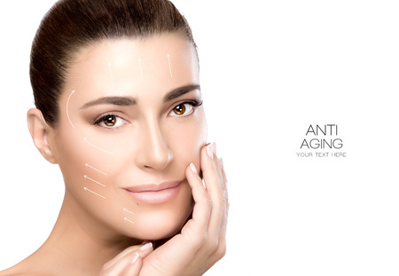 Anti aging treatment and plastic surgery concept. Beautiful young woman with hand on cheek and a friendly expression in a beauty, skincare and spa concepts. Perfect skin. Portrait isolated on white with copy space for text.
