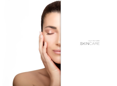 revitalizing: Beautiful young woman with hand on face and closed eyes with a serene expression suitable for skincare and spa concepts. Perfect skin. Beauty portrait isolated on white with copy space alongside for text. Stock Photo