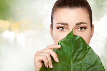 unblemished: Gorgeous young brunette woman with a fresh leaf from a tropical plant held to her face covering mouth and nose in a spa and beauty concept. Portrait over soft green bokeh background with copy space
