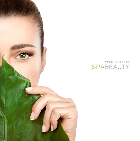 unblemished: Half face woman with a fresh leaf covering mouth and nose in a spa and beauty concept. Beauty portrait isolated on white with copy space for text