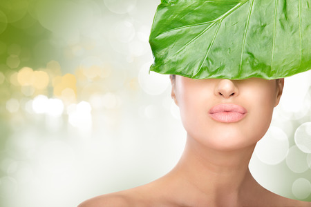 unblemished: Beauty Natural young woman hiding her eyes behind a fresh green leaf while sending a kiss to camera. Closeup portrait against a soft green bokeh background in a spa and wellness concept