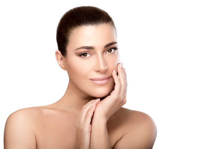 unblemished: Beautiful natural young woman with a smooth unblemished complexion, bare shoulders and hands raised gracefully to her cheek  looking at camera with a friendly expression in a beauty, skincare and spa concept