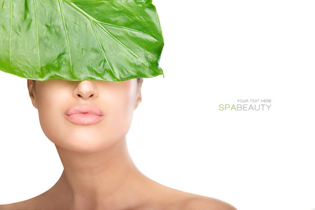 unblemished: Beauty in spa concept with a gorgeous natural woman holding a fresh green leaf to her eyes while sending a kiss to camera. Closeup portrait isolated on white with copyspace for text Stock Photo