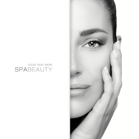 Beauty concept with a gorgeous brunette with copy space on left side of her face which is partially concealed as she holds her hand to neck while looking serenely at the camera. Monochrome portrait isolated on white