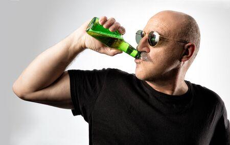 hombre calvo: hombre calvo de mediana edad con gafas de sol disfrutando de una cerveza fr�a beber directamente de la botella con la cabeza girada hacia un lado