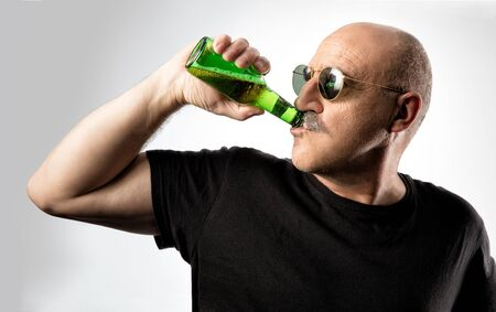 hombre calvo: Middle-aged bald man in sunglasses enjoying a cold beer drinking it directly from the bottle with his head turned to the side