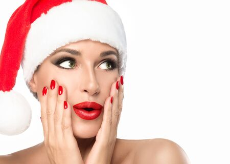 christmas manicure: Christmas woman. Beauty model girl in Santa Claus hat with red lips and matching manicure looking to her left with a surprised expression. Closeup portrait isolated on white background with copy space Stock Photo