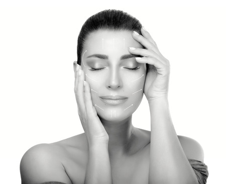 Anti aging treatment and plastic surgery concept. Beautiful young woman with hands on cheeks and eyes closed with a serene expression in a beauty, skincare and spa concepts. Perfect skin. Monochrome portrait isolated on white with copy space Stockfoto
