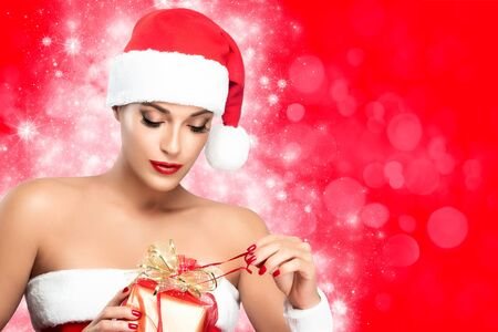 Christmas woman. Beauty model in a festive red Santa hat with matching lips and manicured nails unwrapping gift over red background in red and white Christmas theme with copy space