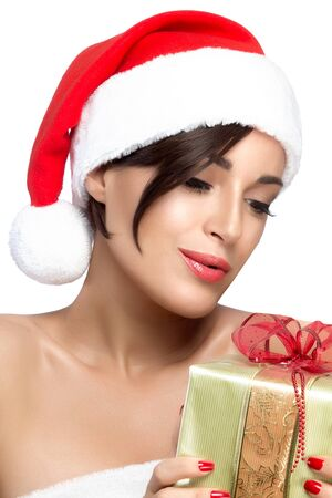 Christmas woman. Close up on single gorgeous young woman in bare shoulders with gift and red Christmas hat over white background