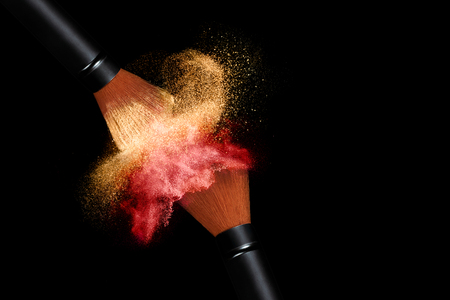 Makeup concept. Stop action view of two makeup brushes applying matching red and gold powder over black background with copy space for text Stock Photo