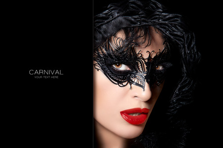 space for text: Sultry mysterious woman in luxury carnival mask with seductive parted lips and red lipstick in a dark hood over a black background in a close up beauty portrait with copy space for text Stock Photo