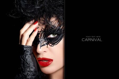 retro dark: Gorgeous sultry dark haired woman with festive makeup wearing a black metallic carnival mask, vivid red lipstick and nail varnish covering one eye with her hand, dark retro theatrical head shot with copy space
