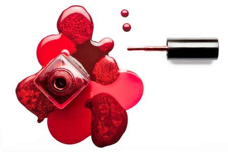 Fine art beauty concept of red and metallic coppery nail varnish puddled artistically around an open bottle with the applicator lying alongside viewed from overhead isolated on white with copy space