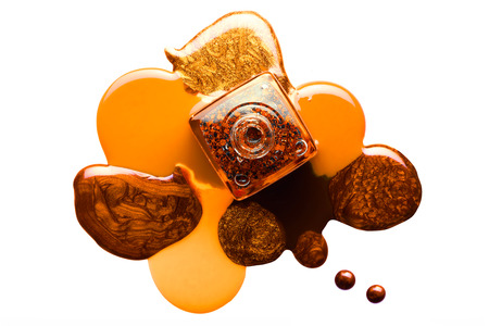 Fine art beauty concept of orange and brown metallic coppery nail varnish puddled artistically around an open bottle viewed from overhead isolated on white with copy space Stock Photo