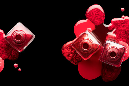 Nail art and manicure concept with metallic red lacquer or nail polish artfully spilled beneath three open bottles. Isolated on a black background, top view with copy space Stock Photo