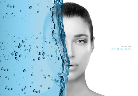 Monochrome greyscale face portrait of a beautiful woman half obscured by a wave of blue in a cropped view isolated on white for a beauty and skin care concept.  Фото со стока