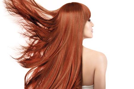 Portrait de beauté d'une jeune femme rousse avec des cheveux longs brillants sains teints dans une couleur cuivrée avec des reflets s'envolant sur le côté dans le vent isolé sur blanc vu de l'arrière Banque d'images