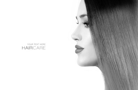 Hair salon concept. Beautiful model girl with gorgeous long straight healthy hair. Keratin Straightening Treatment. Care and hair products. Greyscale beauty portrait isolated on white with copy space.