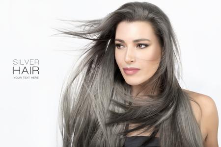 Schönheitsporträt einer attraktiven jungen Frau mit langen trendigen silbergrauen Haaren, die um ihr Gesicht in einer Brise wehten, lokalisiert auf Weiß in einem Haarpflege- und Glamourkonzept