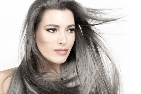 Attractive young woman with long trendy silver hair blowing in a breeze.