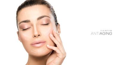Anti-aging behandeling en plastische chirurgie concept. Mooie jonge vrouw met hand op wang en ogen gesloten met een serene uitdrukking en witte pijlen over gezicht. Geïsoleerd op wit met kopie ruimte Stockfoto