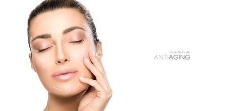 Anti aging treatment and plastic surgery concept. Beautiful young woman with hand on cheek and eyes closed with a serene expression and white arrows over face. Isolated on white with copy space Stock Photo