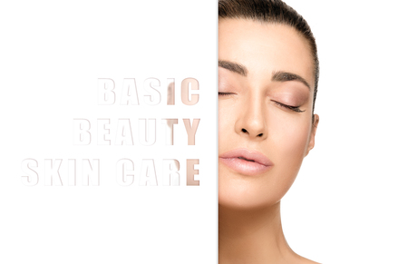 Beautiful natural woman with flawless skin, closed eyes and parted lips in a Basic Beauty Skin Care concept with text on a sign half obscuring her face