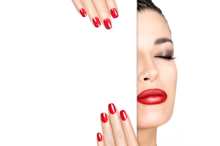 Beauty Makeup Concept. Beautiful fashion model girl with smoky eye and lipstick in red to match her manicured nails Zdjęcie Seryjne