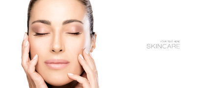Beautiful natural young woman face in skin care concept, with hands on cheeks and eyes closed with a serene expression isolated on white with copy space.