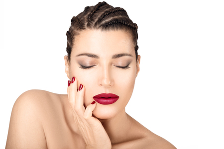 Beautiful model girl with fashion bright makeup, red lips and nails touching her face with closed eyes. Zdjęcie Seryjne