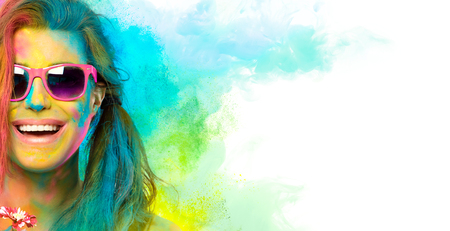 Beautiful joyful young woman celebrating Holi festival of colors, covered in rainbow colored powder with pink sunglasses smiling at camera.