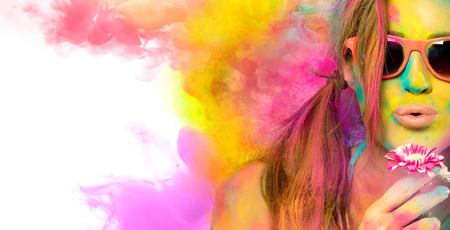 Beautiful young woman wearing stylish sunglasses blowing on a flower celebrating Zdjęcie Seryjne