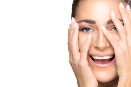 Healthy skin beautiful young woman with hands raised to her face with a wow expression in a skincare, wellness and anti-aging concept.